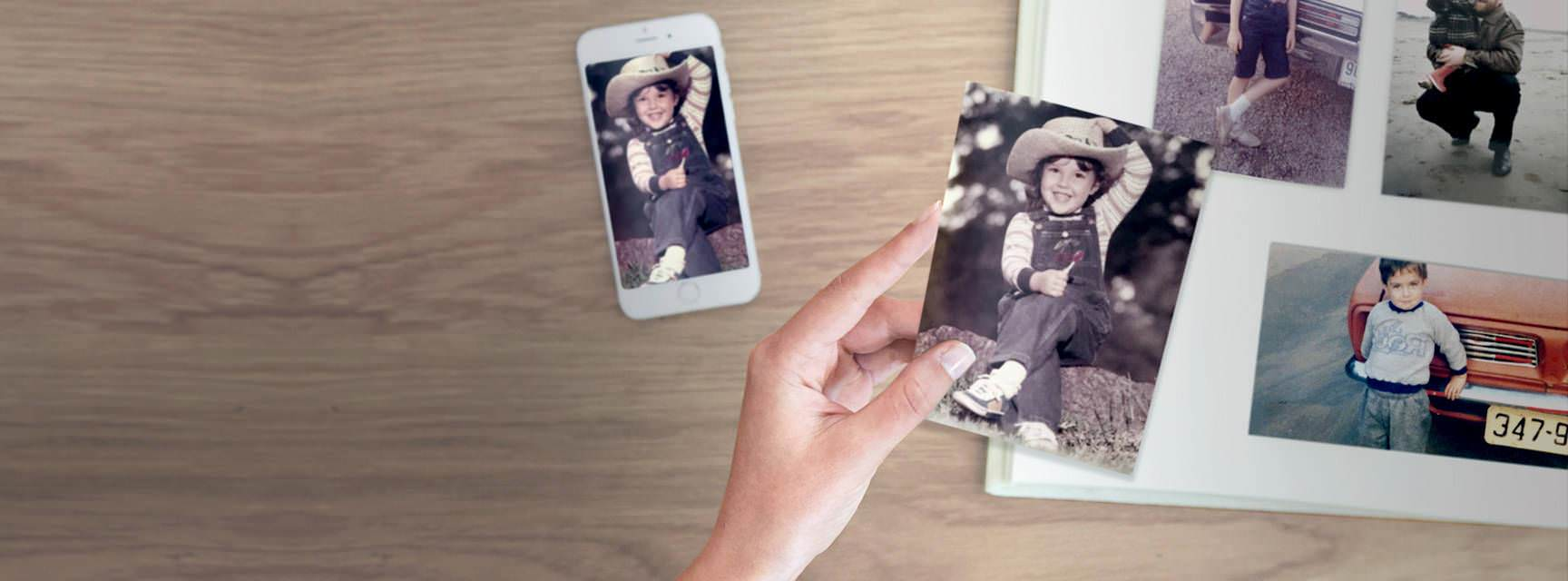 iPhone showing a scanned photo in the Photomyne app next to a paper photo album with the same photo, printed