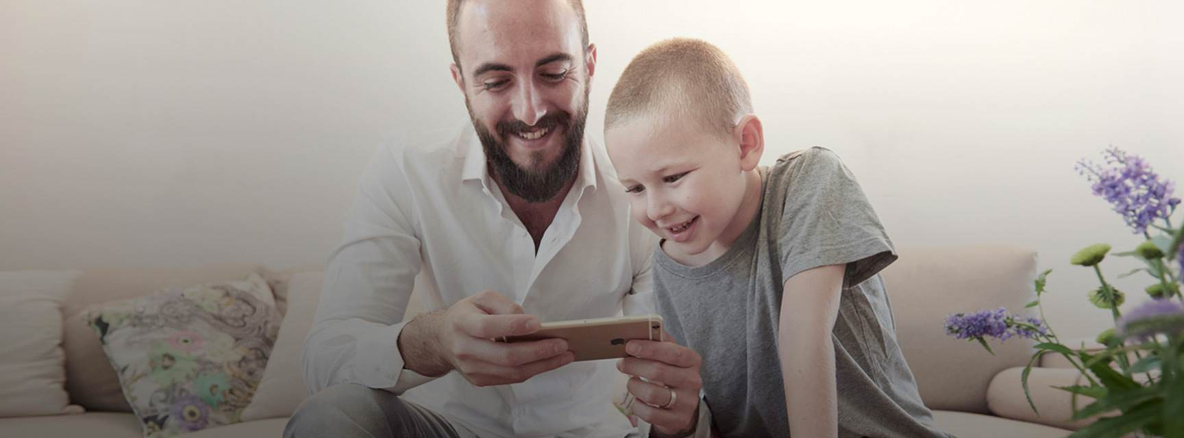 Father and son, watching together scanned photos on a smartphone using the Photomyne app